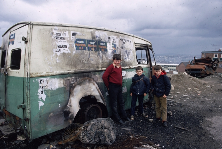 circa 1975: Three children gather by a burnt out van plastered with IRA posters, in the predominantly Catholic Bogside area of Londonderry. (Photo by Keystone/Getty Images) http://flashbak.com/photos-of-children-in-the-troubles-northern-ireland-1969-1981-53649/