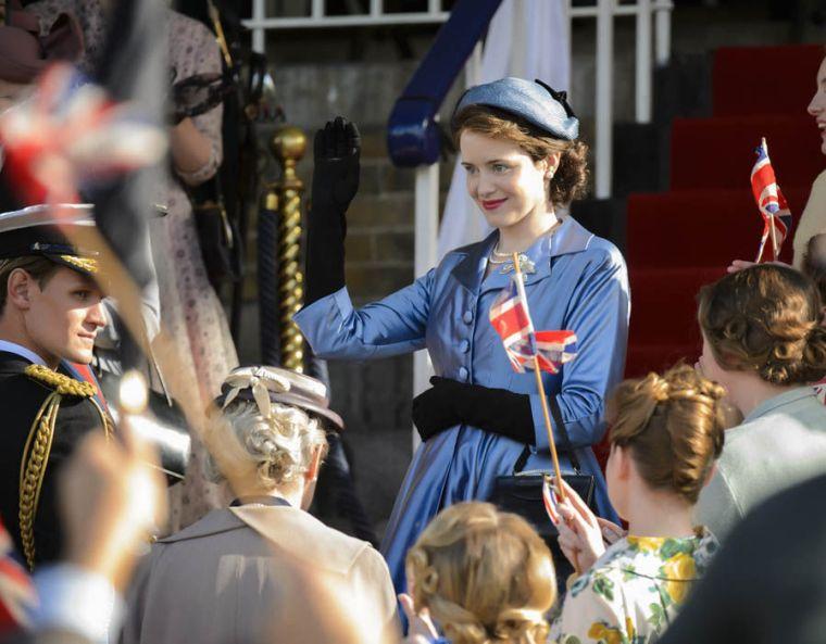 Queen Elisabeth II (Claire Foy) salue la foule avec son époux Philip Mountbatten (Matt Smith) dans The Crown, création Netflix © Netflix
