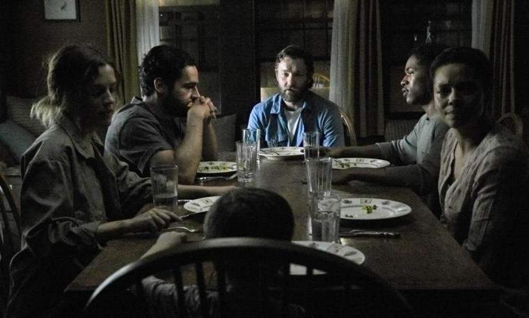 Paul (Joel Edgerton) et sa famille reçoivent à leur table Will (Christopher Abbott), sa femme Kim (Riley Keough) et leur jeune enfant Andrew (Griffin Robert Faulkner). © Mars Films